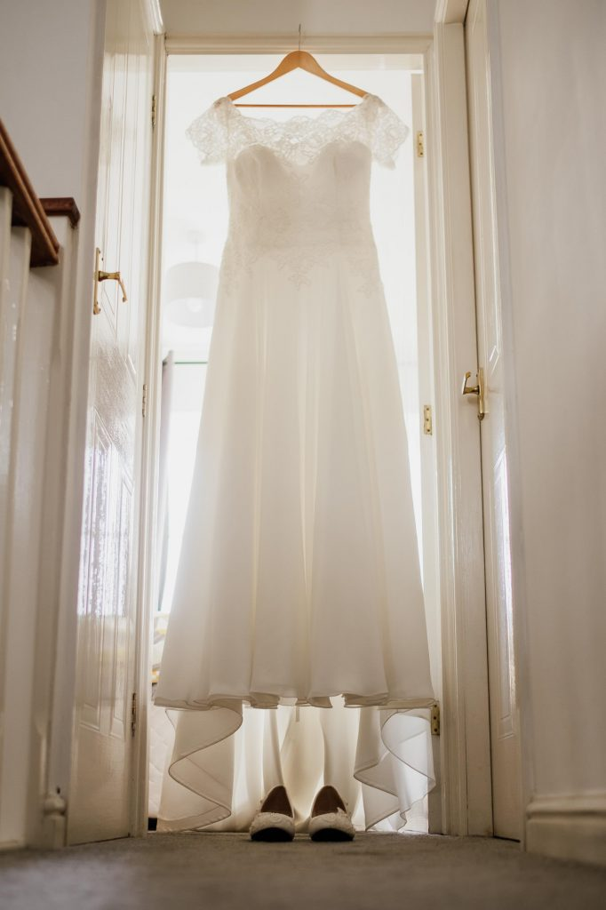 Hanging wedding dress with shoes underneath