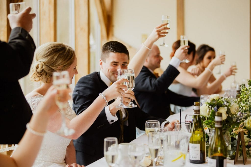 Bride and groom toast during speeches