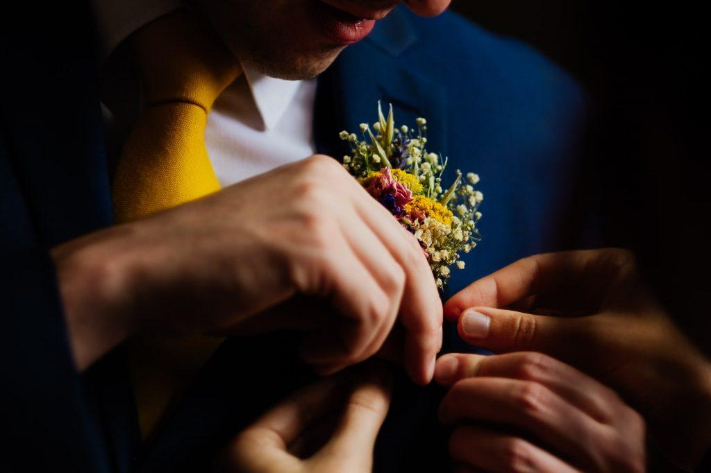 Pinning on groomsman button hole