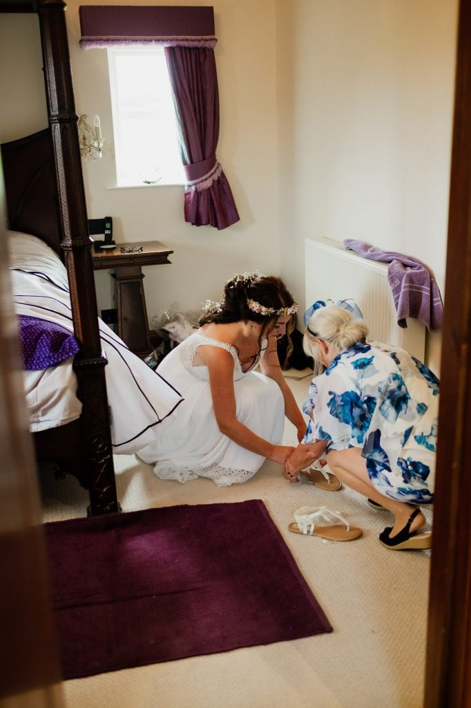 Mother helping bride with wedding shoes