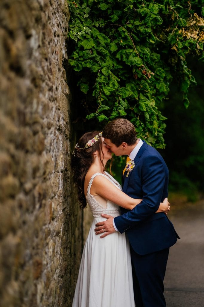 Bride and groom kiss by stone wall