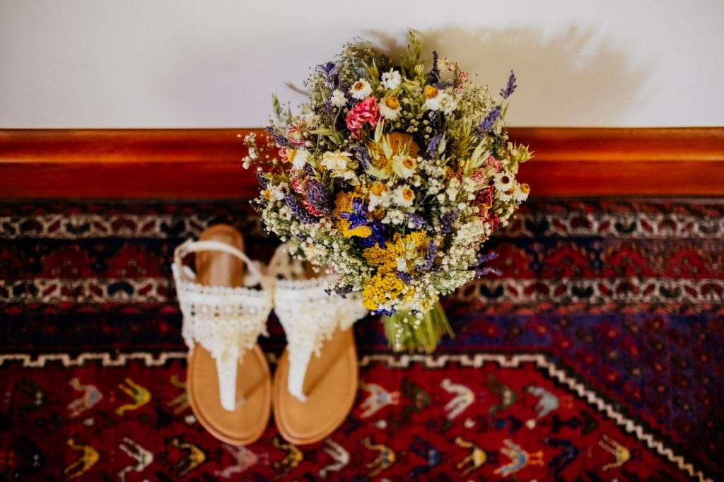 Dried flowers and wedding sandals on patterned rug