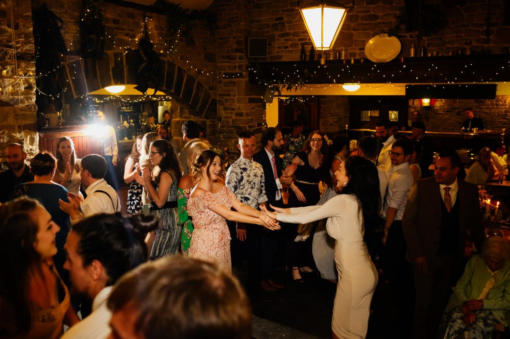 Guests mid ceilidh at wedding reception