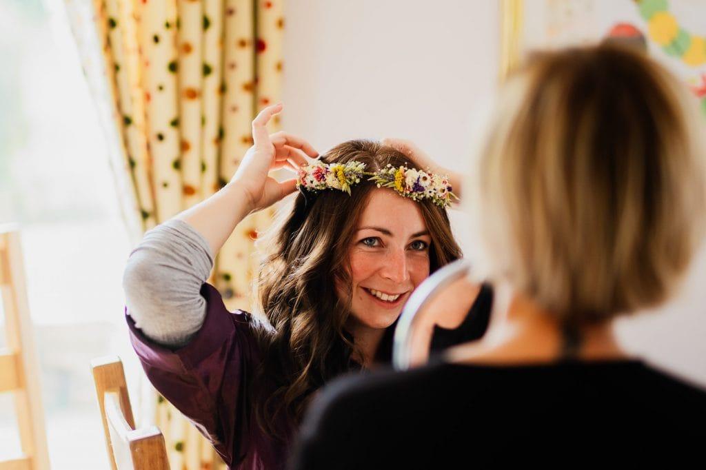 Bride positioning flower crown in mirror