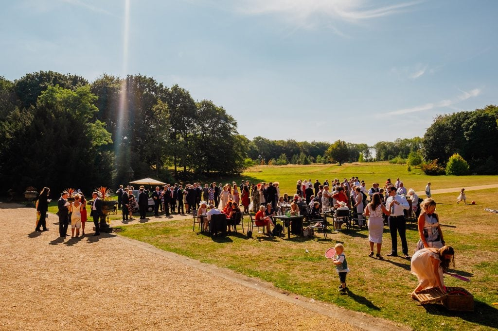 Wedding guests in venue grounds in summer