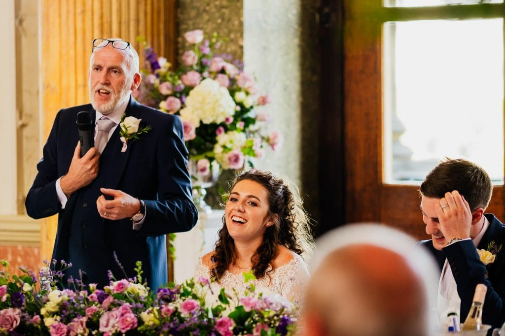 Bride laughing during dads speech