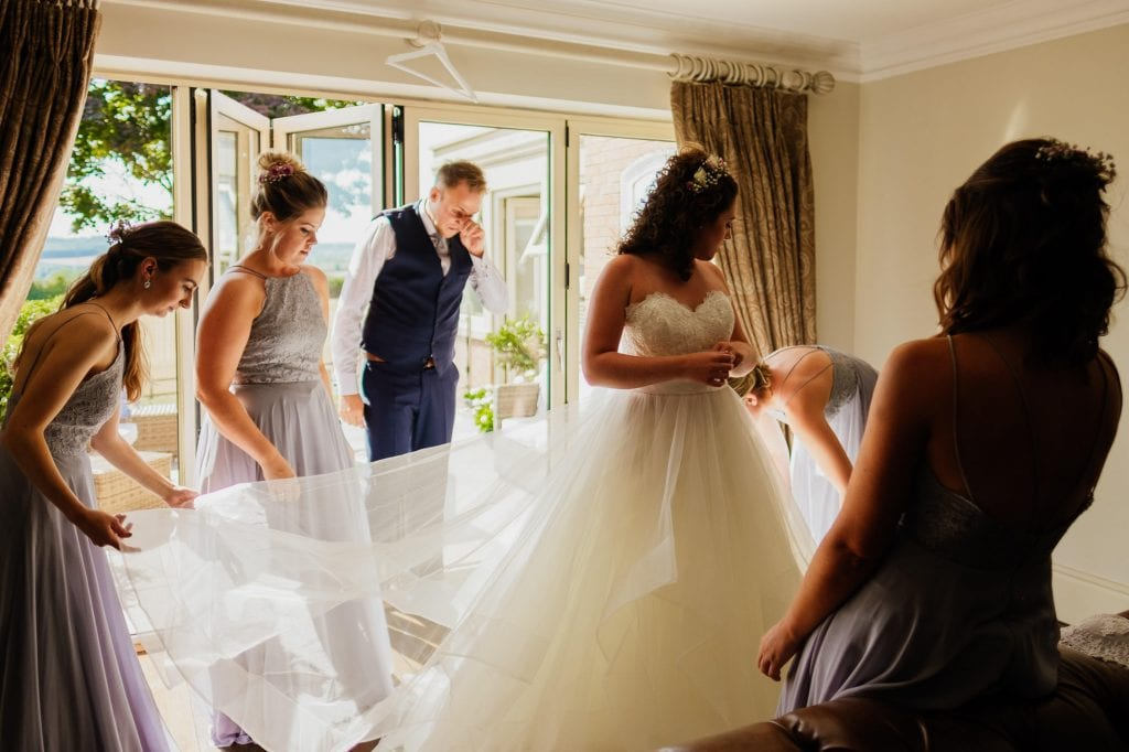 helping the bride into wedding dress