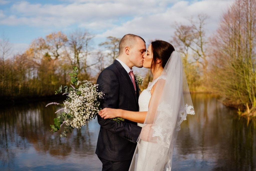 bride and groom kiss at lake in sun