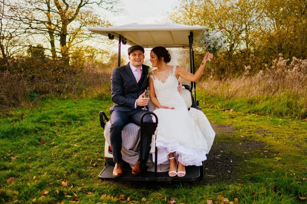 just married couple celebrate on a golf buggy