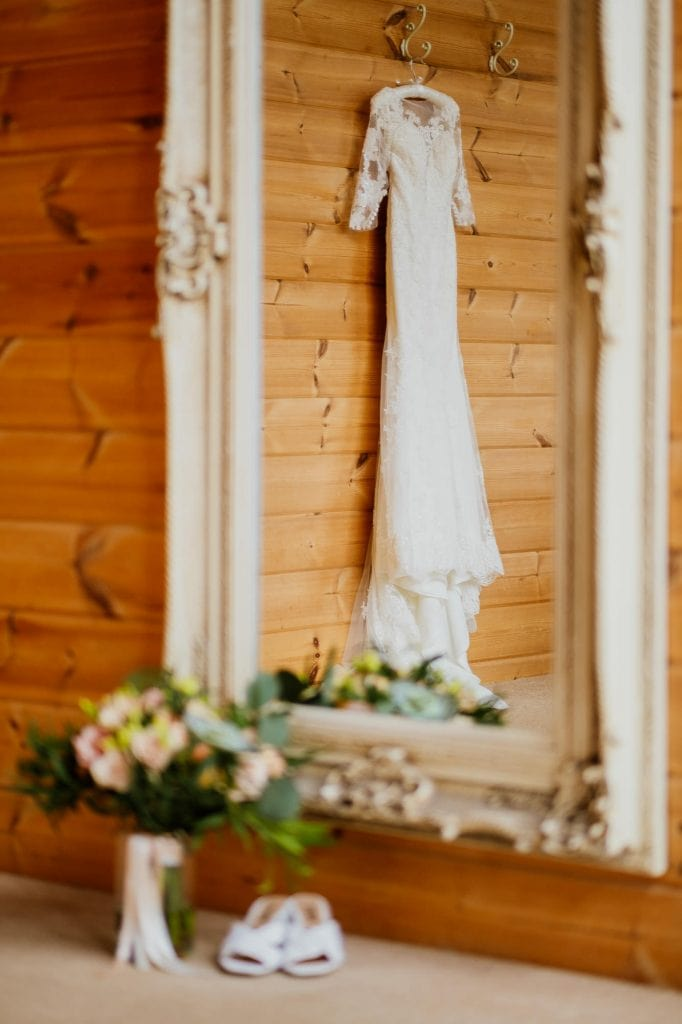wedding dress hanging in mirror