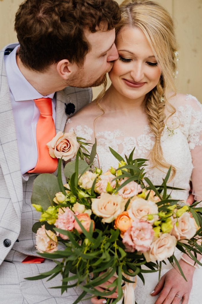 groom kisses brides cheek