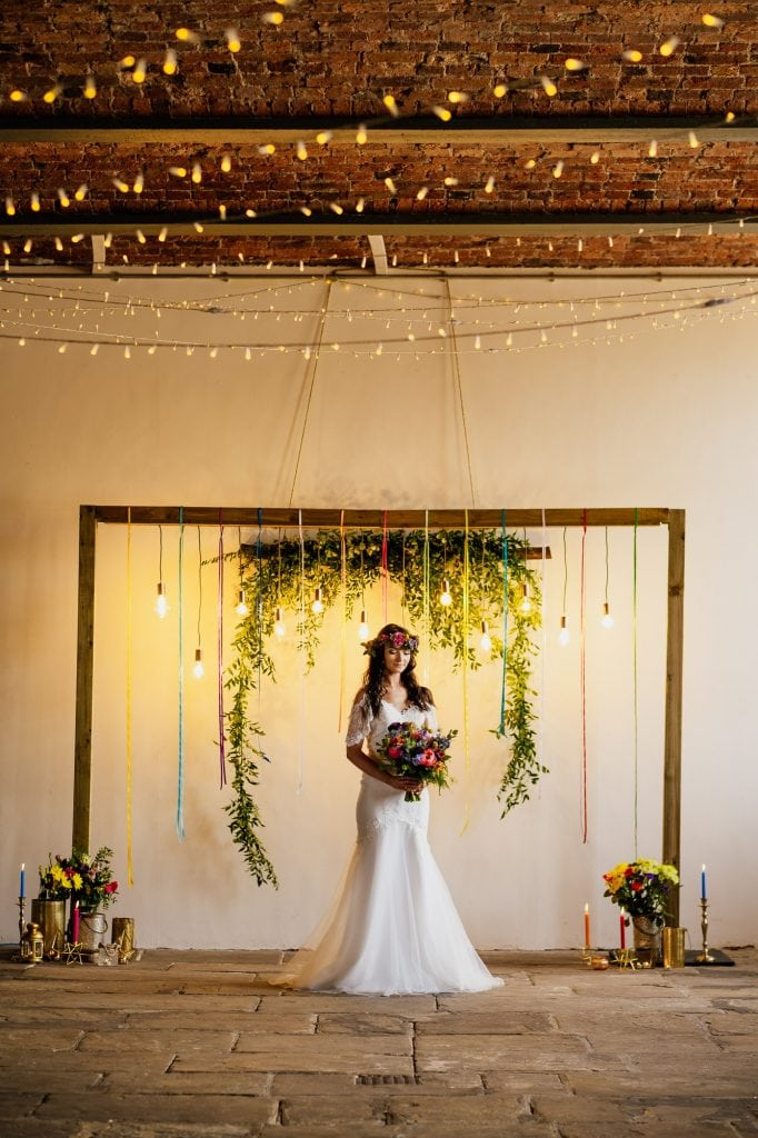 bride under wedding arch