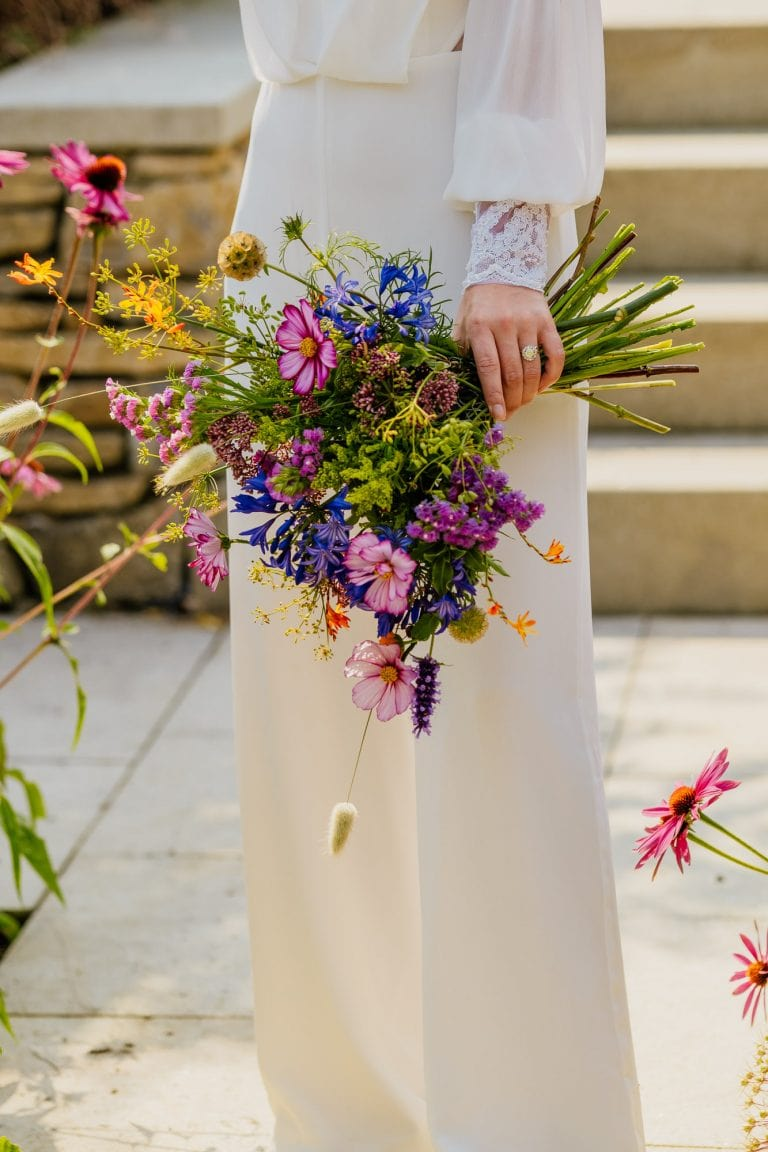 colourful summer wedding bouquet and bridal jumpsuit