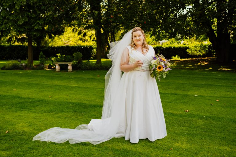 Bride stood with champagne and flowers in garden